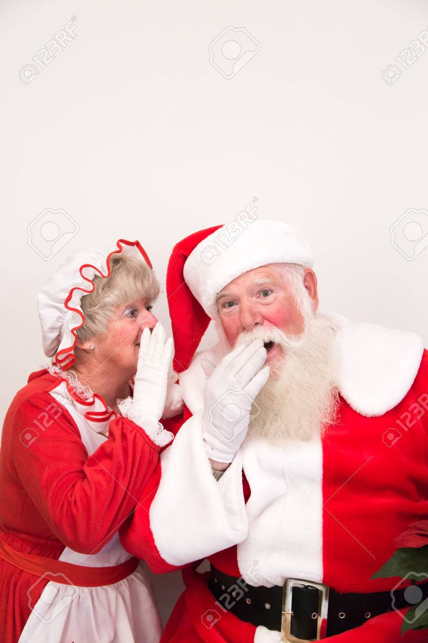 Mrs Claus whispers a secret into Santa - 34613348
