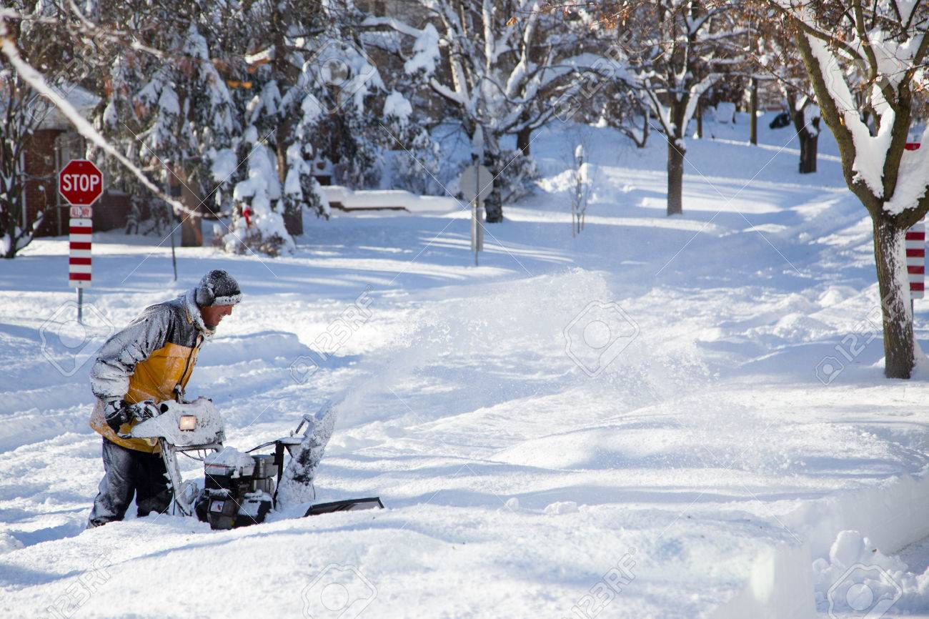 A thick layer of snow covers the road as a man with a snow blower tries to find his walkway to clear - 39648439