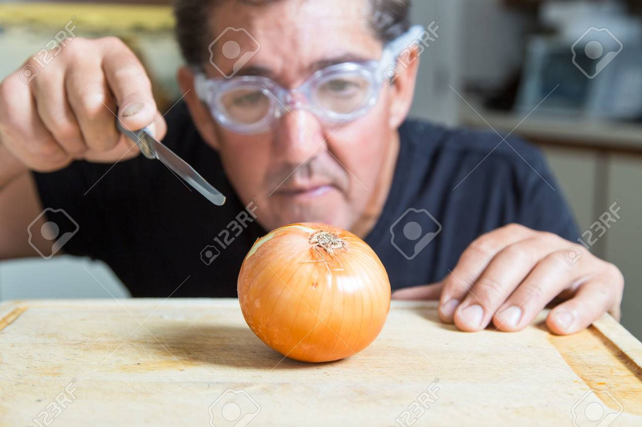 A man in the kitchen tries to cut an onion using goggles to avoid tears - 48108143