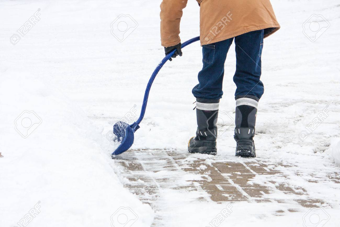 A man with a curved handled snow shovel clearing snow from a brick sidewalk in Canadian winter. - 48744553