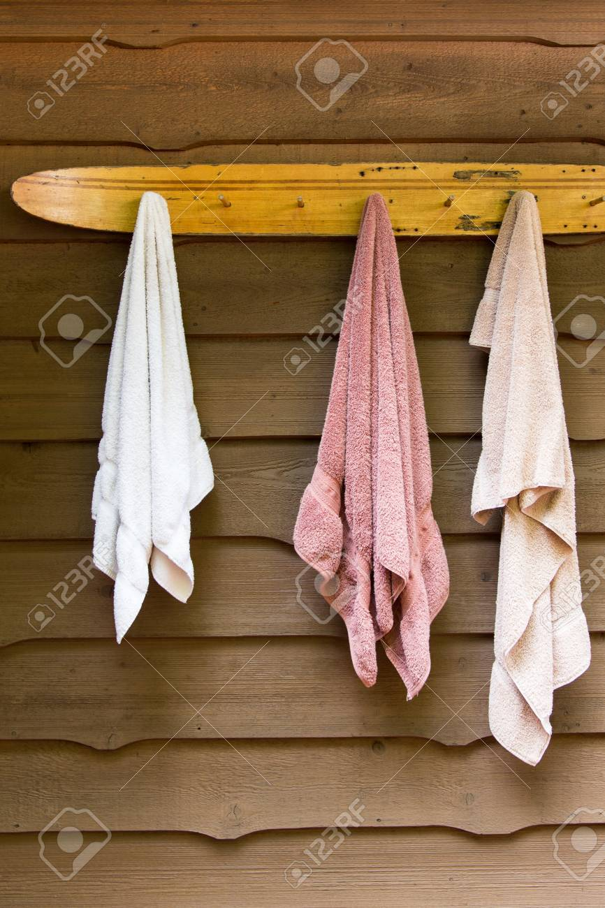 swimming towels hang from a vintage water ski rack at the cottage in summer - 65782621