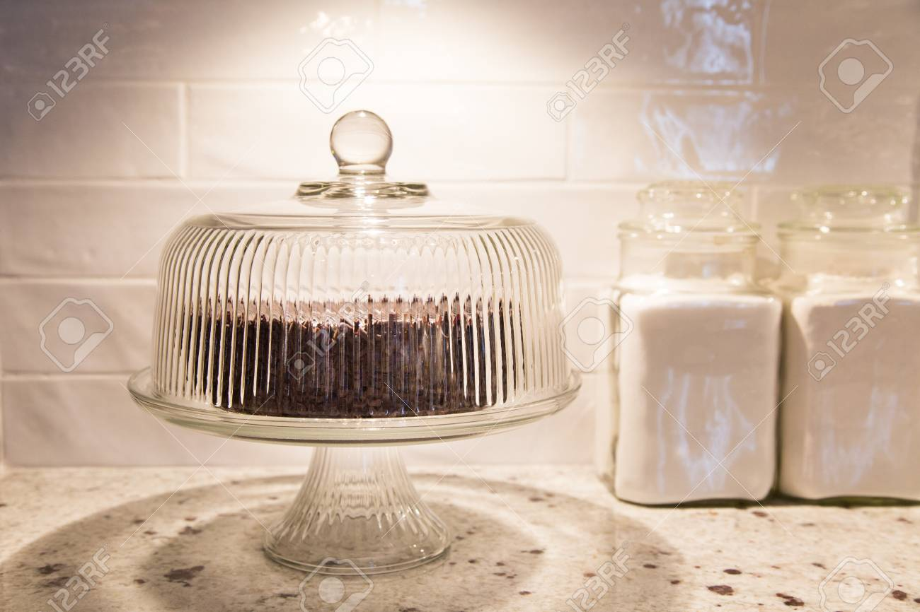 chocolate cake under a vintage glass cake dome with vintage canisters beside stock photo 78365857 - Glass Cake Dome