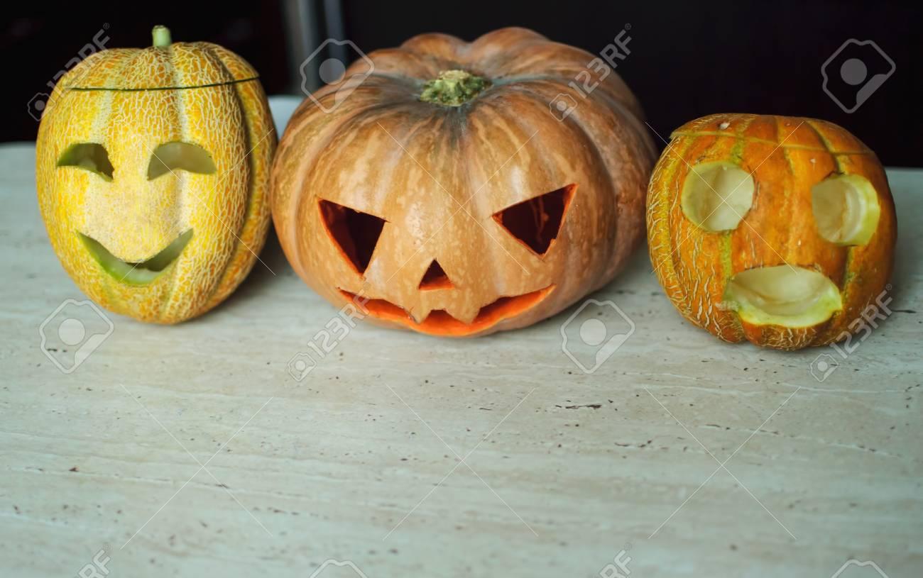 Tre lanterne da zucca e meloni sul tavolo della cucina. Priorità bassa di  Halloween di concetto