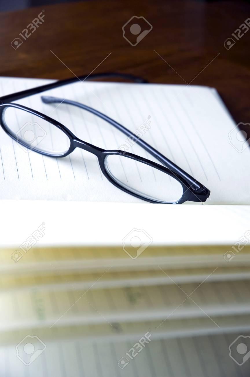 07f71ec099 black frame eyeglasses put on notebook Stock Photo - 17299911