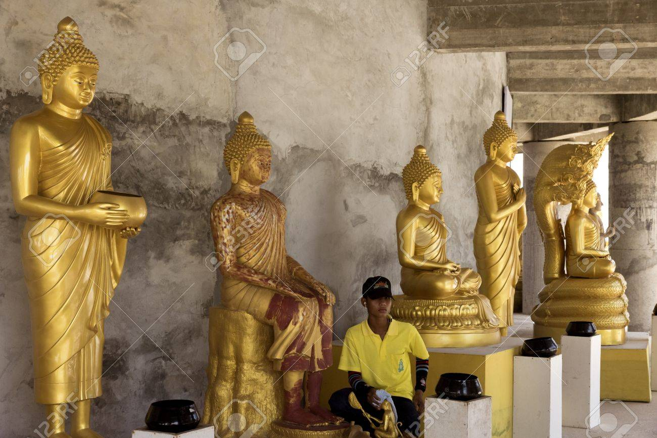 PHUKET, THAILAND FEBRUARY 15 2013: A groundskeeper at the Big Buddha Statue, an iconic symbol of Thai Buddhism in Phuket, cleans the many Buddha statues encircling the base of the monument. Stock Photo - 19639753
