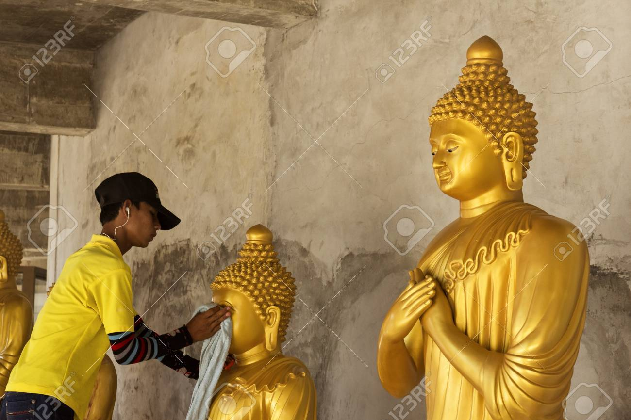 PHUKET, THAILAND FEBRUARY 15 2013: A groundskeeper at the Big Buddha Statue, an iconic symbol of Thai Buddhism in Phuket, cleans a statue of Buddha at the base of the monument. Stock Photo - 19680289