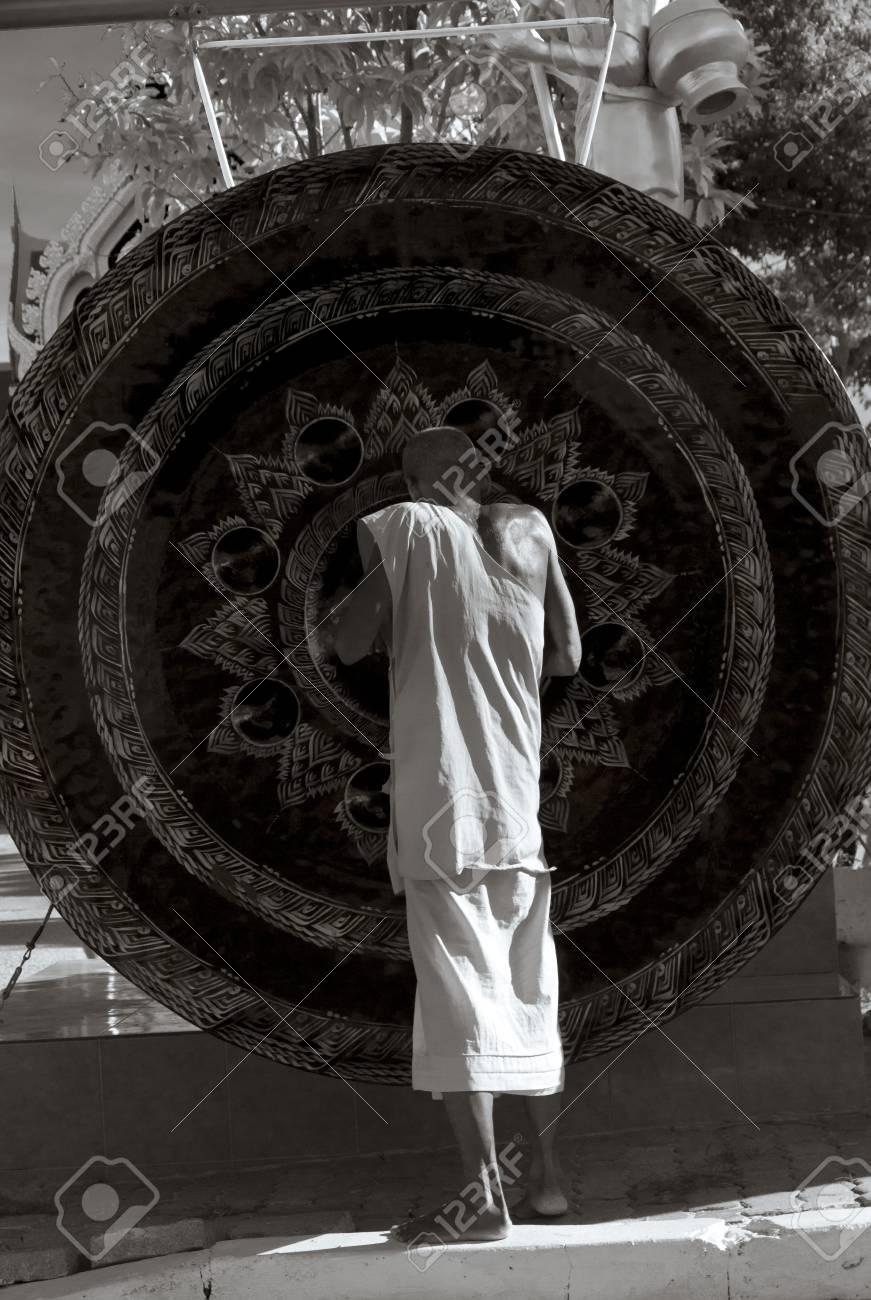 WAT KARON MARKET, KARON, PHUKET, THAILAND FEBRUARY 8 2013: A monk in the courtyard of Temple Karong in Phuket rubs a large gong to make it ring. Stock Photo - 20264092
