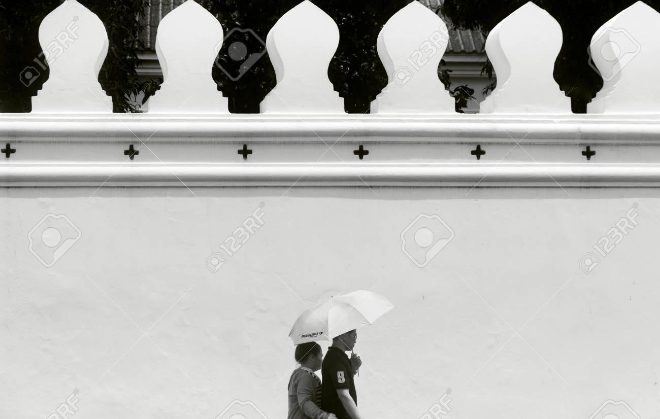 GRAND PALACE, BANGKOK, THAILAND, 26 SEPTEMBER 2014: A couple hold a sun umbrella as they walk past the perimeter wall of the Grand Palace in Bangkok. - 32535367