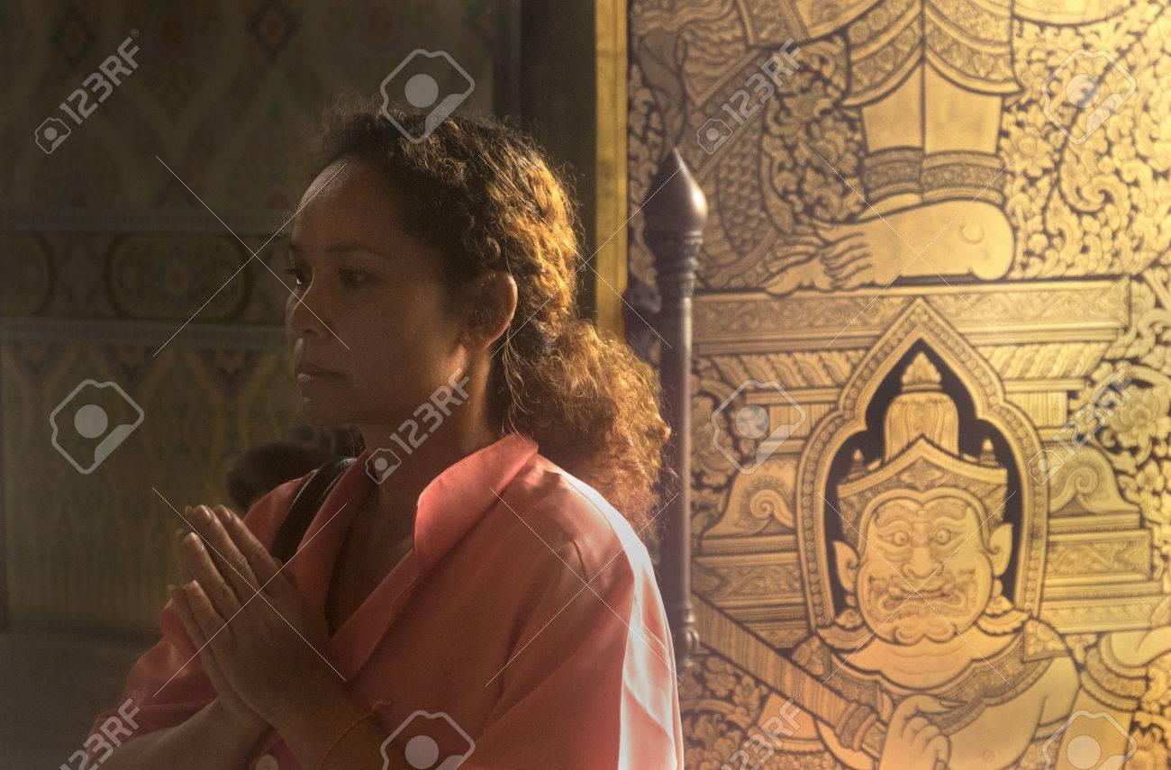 GOLDEN BUDDHA TEMPLE, BANGKOK, THAILAND, 28 SEPTEMBER 2014: A Thai woman says a prayer to the Gold Buddha during a visit - 32534329