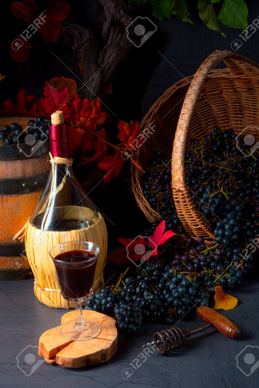 Grapes in the basket with wine and tree leaves - 158816883