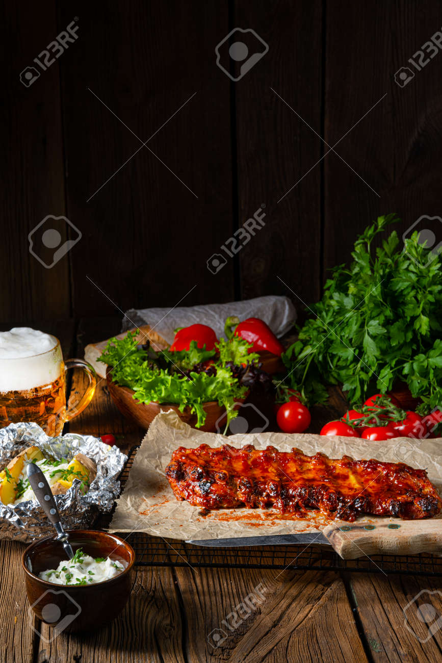 Spicy spare ribs with baked potatoes and sour cream - 168502348