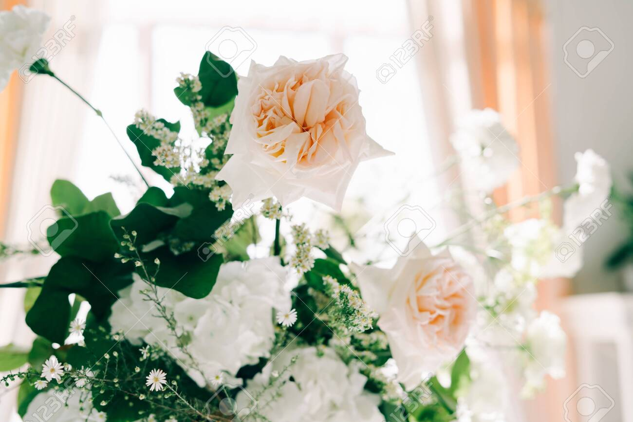 beautiful floral arrangement of delicate rose flowers and fresh greenery in the design of the wedding table - 140388201