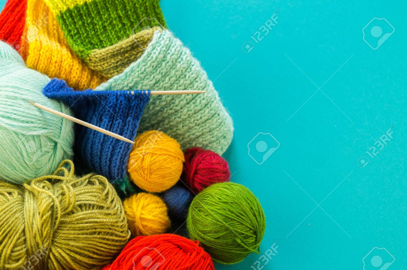 Knitting a rainbow scarf and hat. Basket with balls of wool, knitting needles. Blue background. Favorite work is a hobby. - 107647072