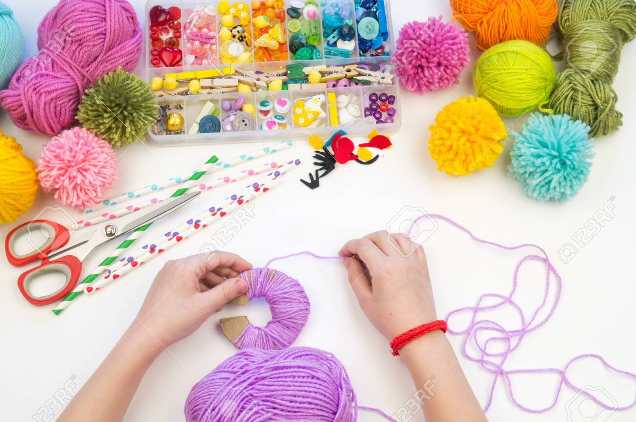 The child is engaged in a favorite hobby. The kid makes a pom-pom from a woolen thread monster. Holiday toy gift. Creativity with children. School kindergarten. Material for crafts. - 122560000