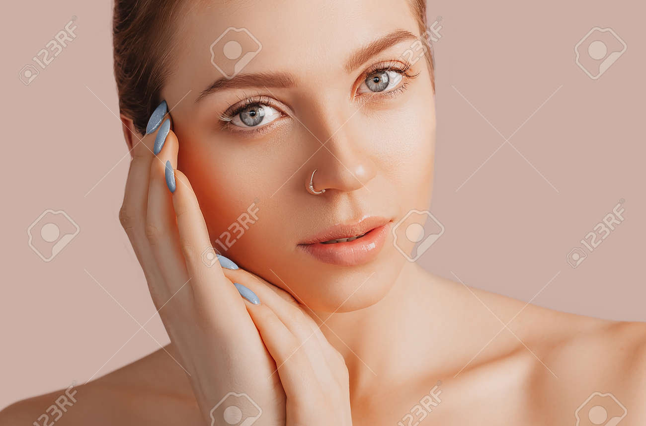 Beautiful sensual young girl with clean skin on a beige background with a mockup. Topless woman in a towel. The concept of spa treatments, natural beauty and care, youth, cream and mask, freshness - 168093024