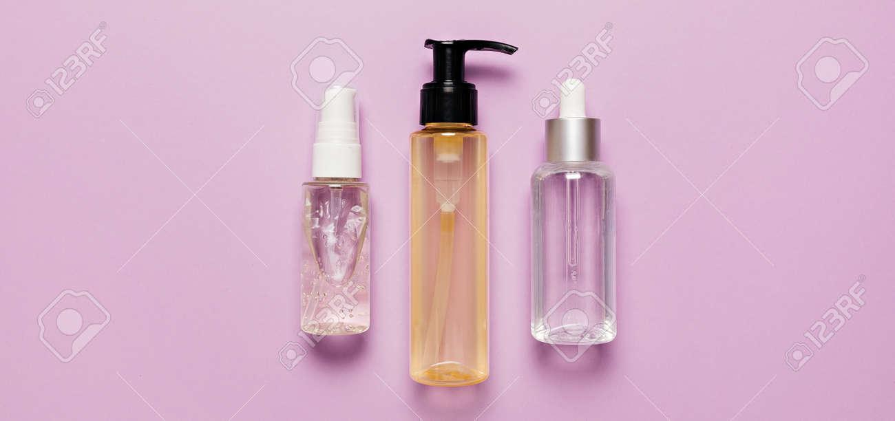 Organic cosmetics packaging design. Flat lay, top view clear glass pump bottle, brush jar, moisturizing serum jar on a purple background. Natural cosmetics SPA - 173643301
