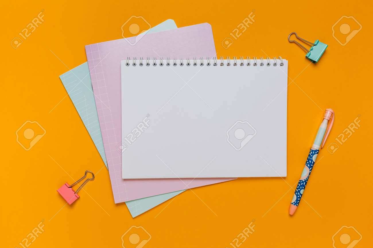Notepad, exercise book and pen on the desk. Mock up in copy space office on orange background. Back to school - 173643983
