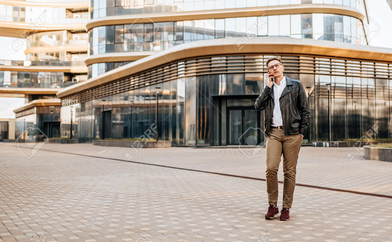 Handsome man with glasses with a smartphone on the street of a big city. Businessman talking on the phone on urban background - 173643935
