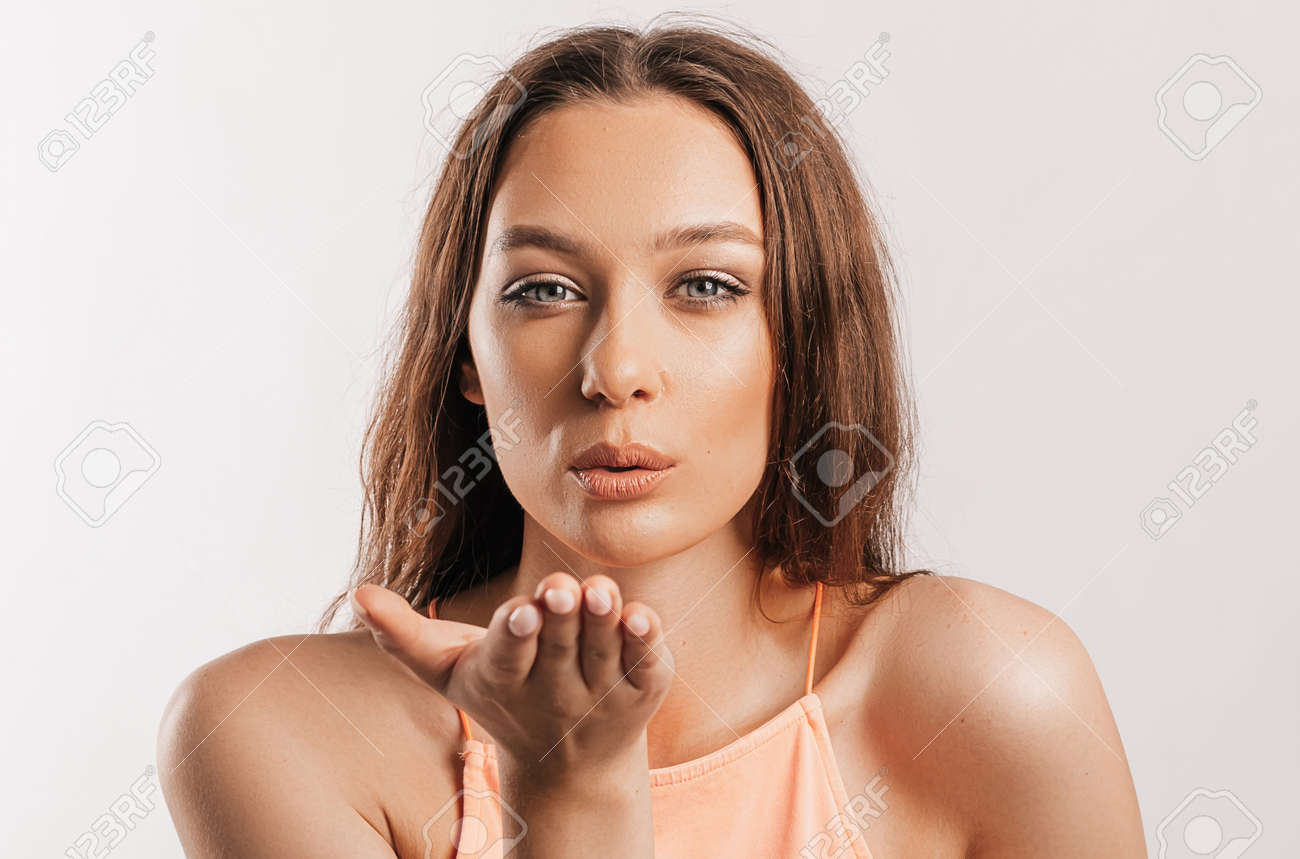Beautiful young girl blows a kiss and posing looking at the camera on a white isolated background. Positive brunette woman. Kind look. Beauty face. - 173643451