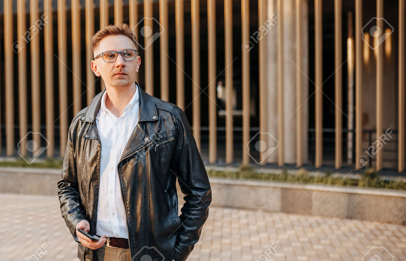 Handsome man with glasses with a smartphone on the street of a big city. Businessman talking on the phone on urban background - 173643975
