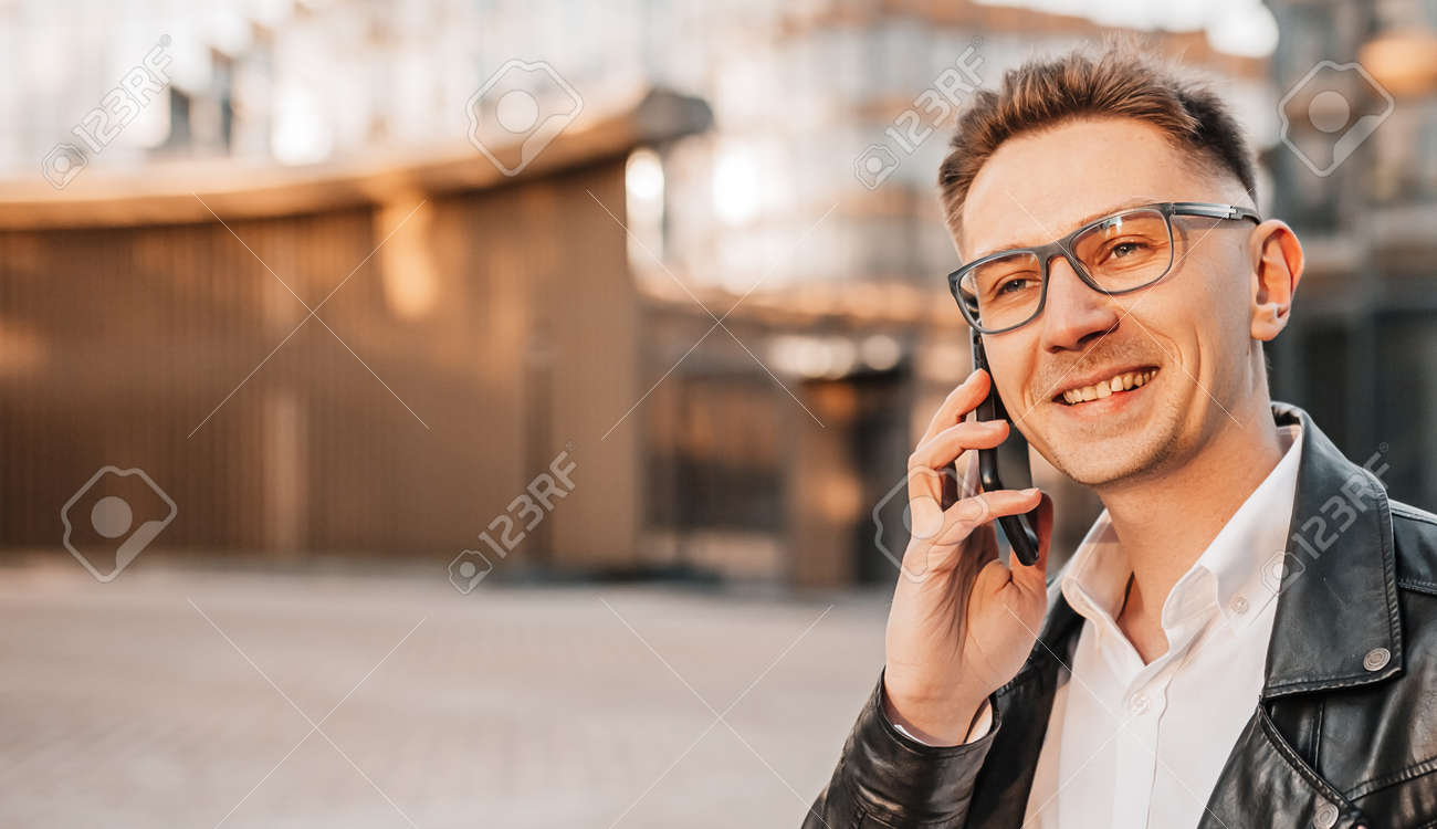 Handsome man with glasses with a smartphone on the street of a big city. Businessman talking on the phone on urban background - 173643949