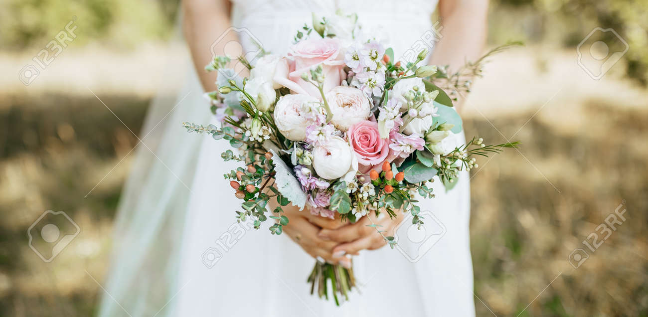 Bride holding wedding bouquet with white and pink flowers - 173757584