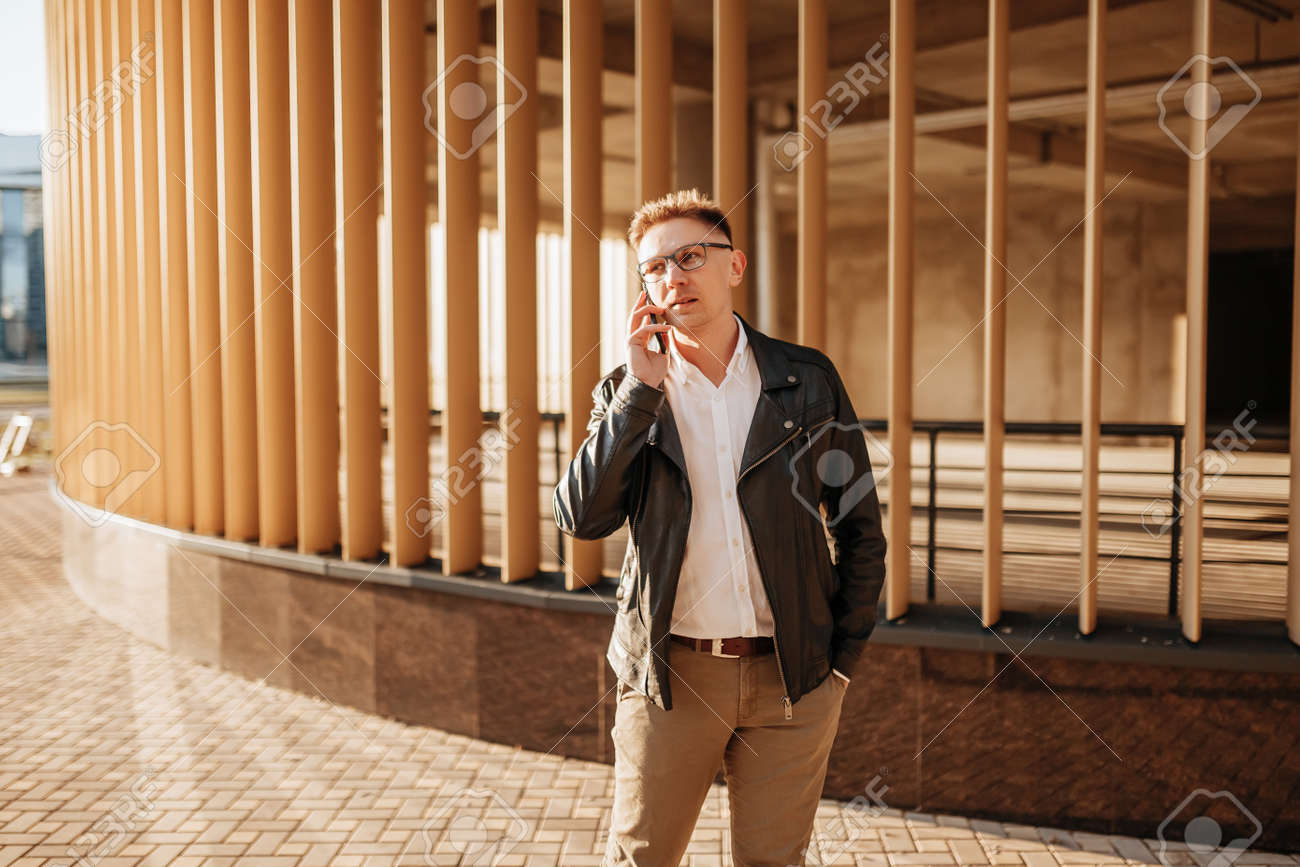Handsome man with glasses with a smartphone on the street of a big city. Businessman talking on the phone on urban background - 173757233
