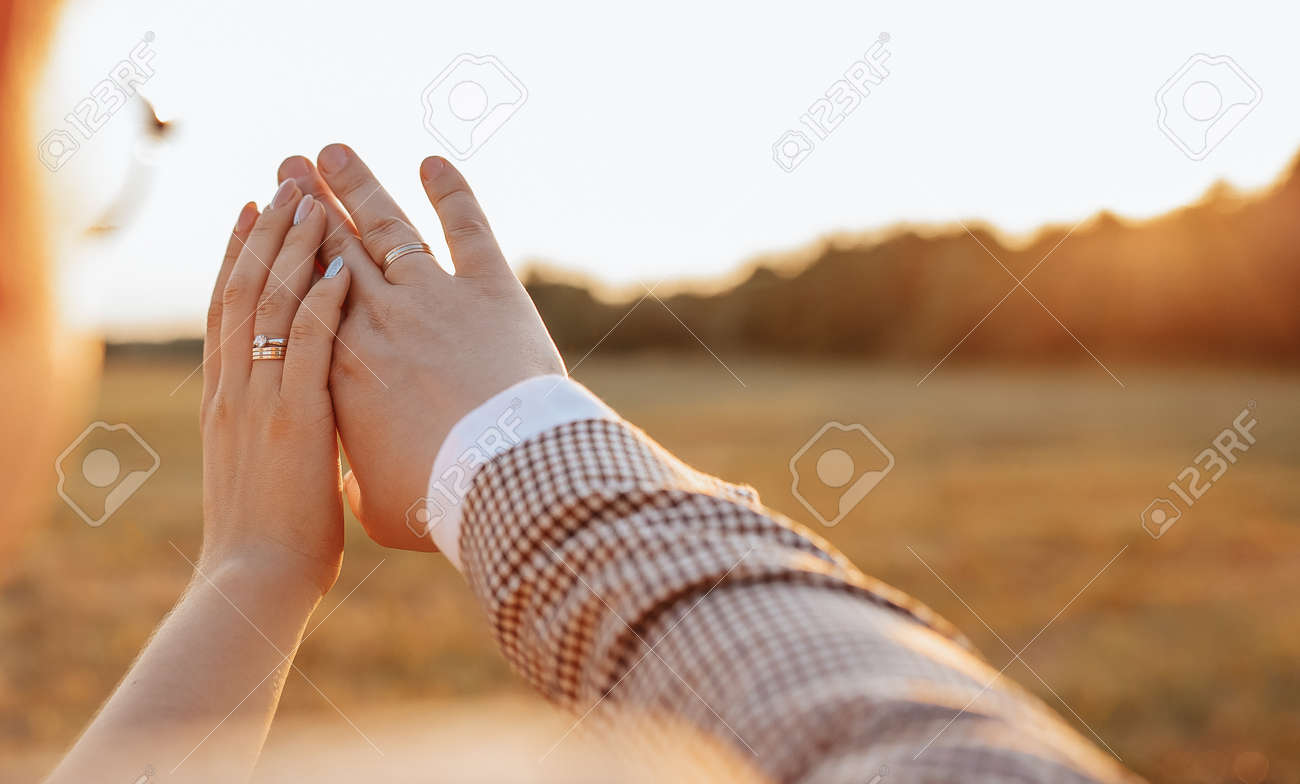 Bride and groom on wedding day hug and show rings at sunset - 173799745