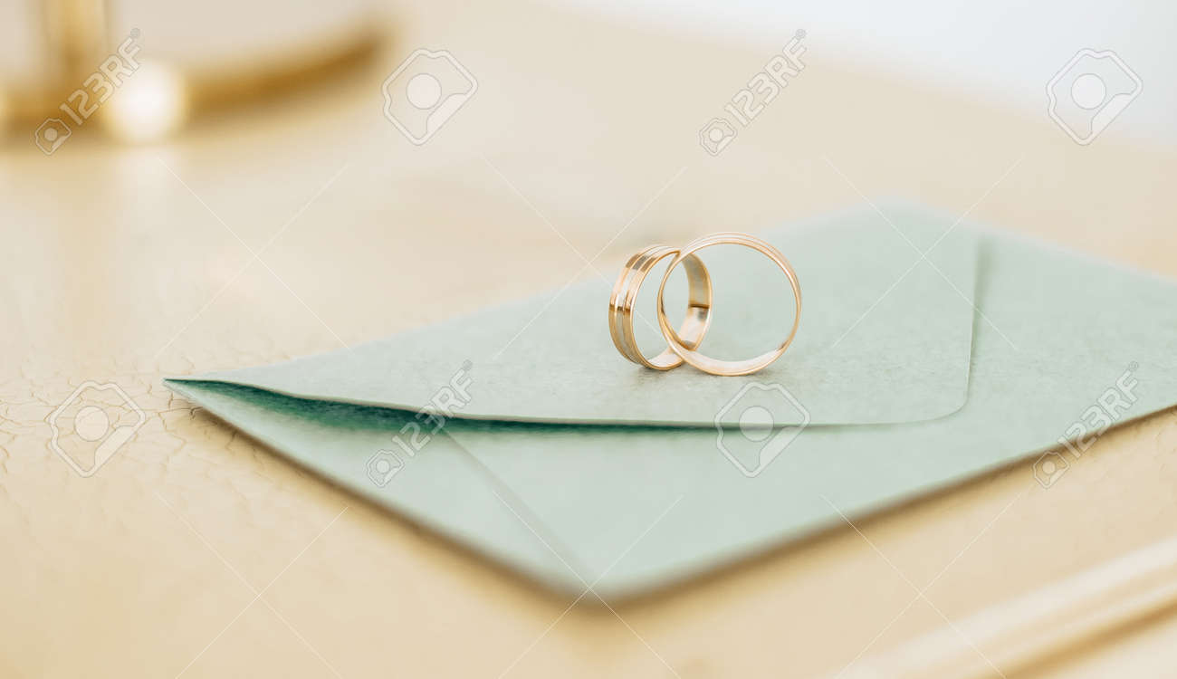 Two wedding rings lie on an invitation with gold background - 173799907