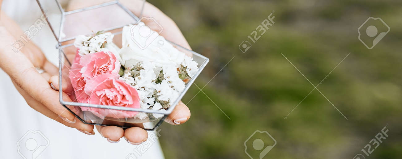 Bride holding wedding box for rings with white and pink flowers - 173799429