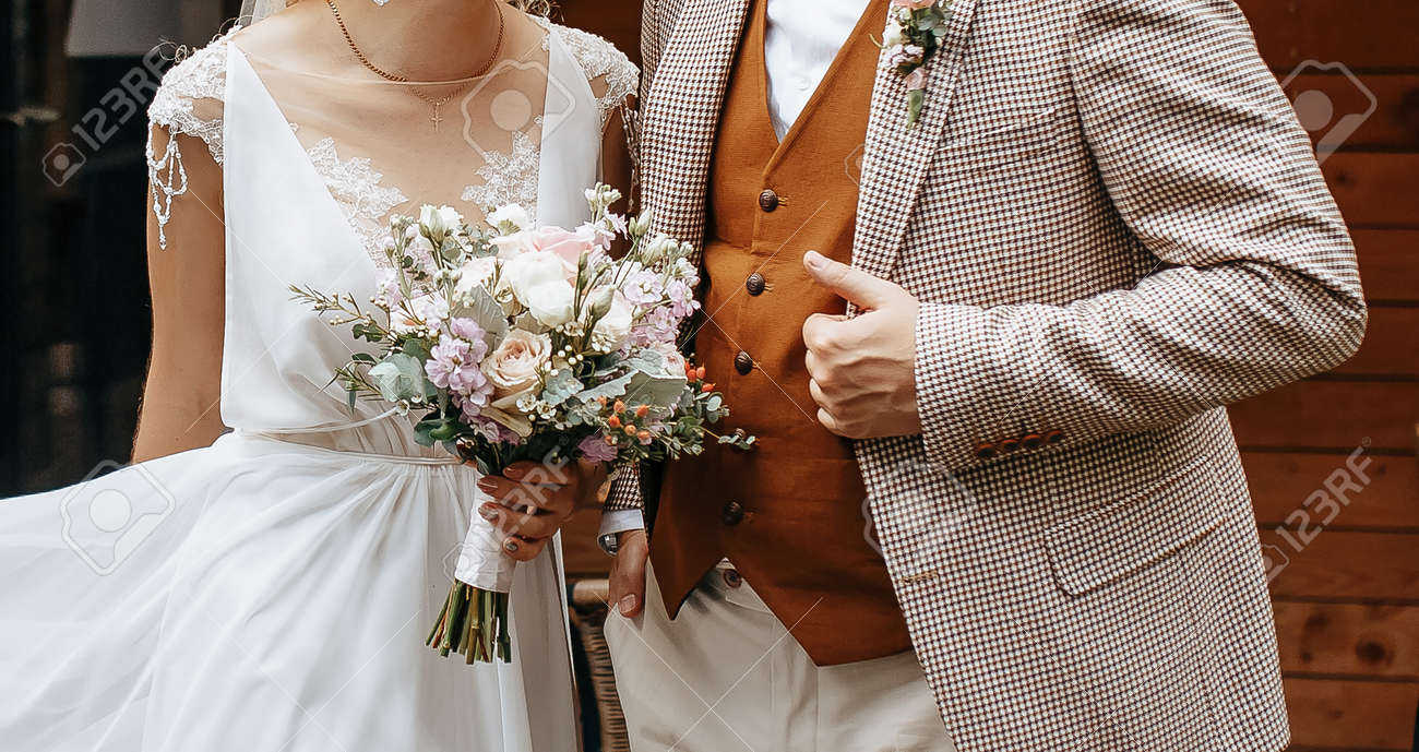 Bride and groom on wedding day hug and show love with a wedding bouquet of rose flowers - 173799806
