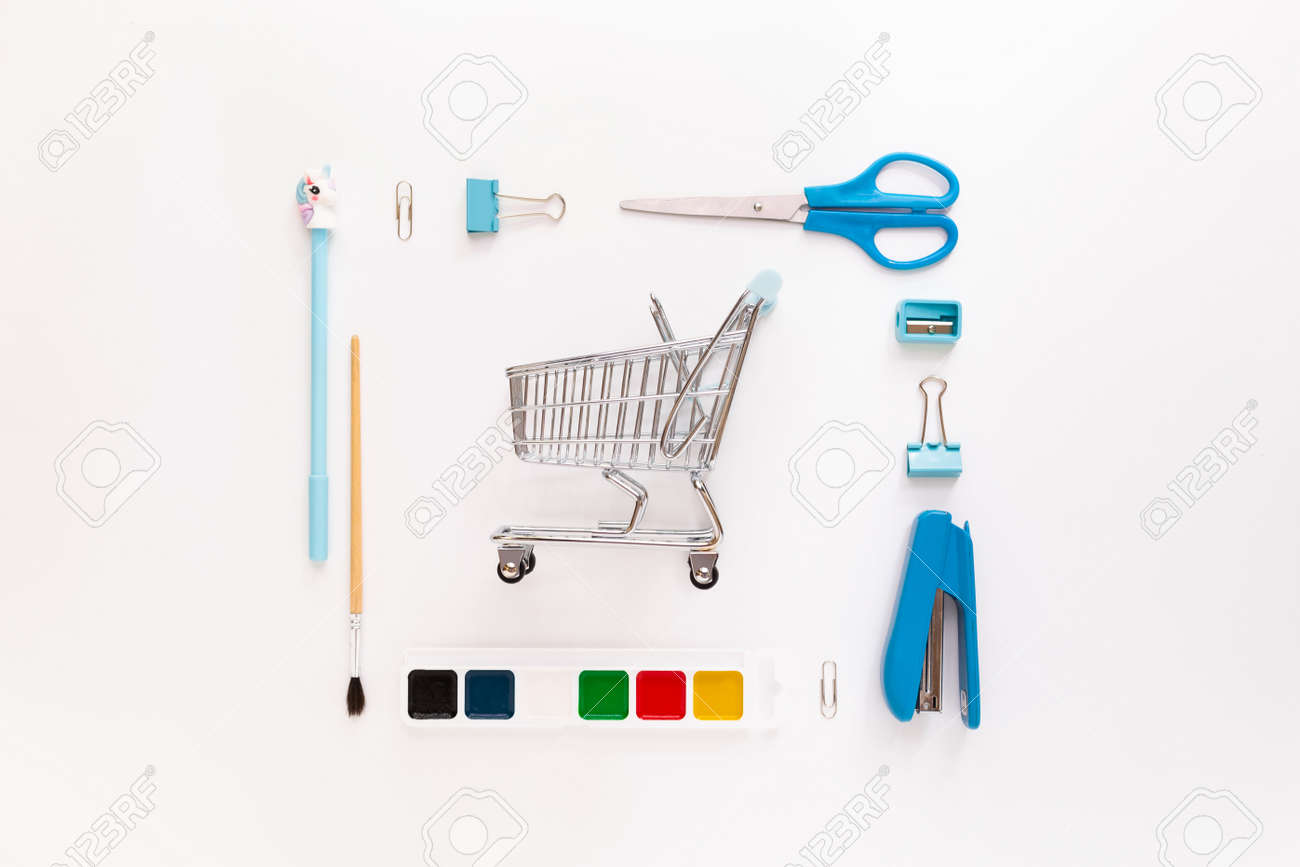 Top view of modern white blue office desktop with school supplies and stationery on table with basket or shopping trolley. Back to school concept flat lay with mockup - 173923601