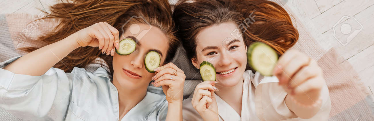 Two girls make homemade face and hair beauty masks. Cucumbers for the freshness of the skin around the eyes. Women take care of youthful skin. Girlfriends laugh at home lying on the floor on pillows. - 173923338