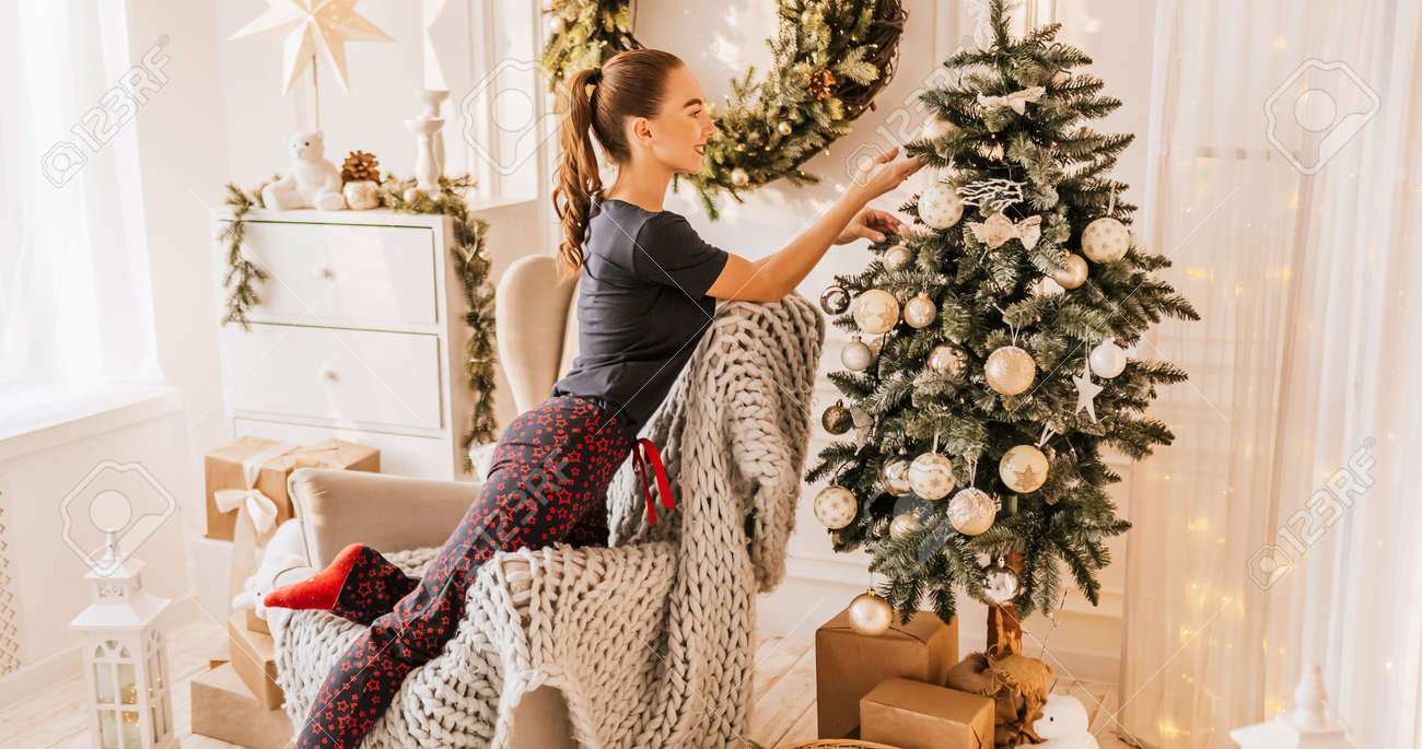 Beautiful cheerful happy young girl with christmas gifts on sofa on the background of a new year tree at home - 173923637