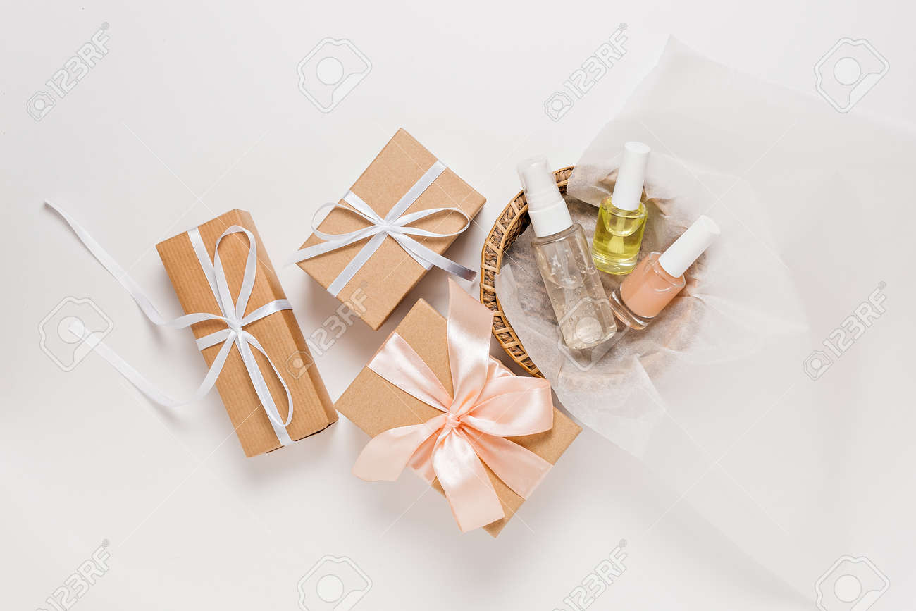 Organic cosmetics and gifts for the holiday. Flat lay, top view clear glass pump bottle, brush jar, moisturizing serum jar in a paper basket on a white background. Natural cosmetics SPA - 173923365