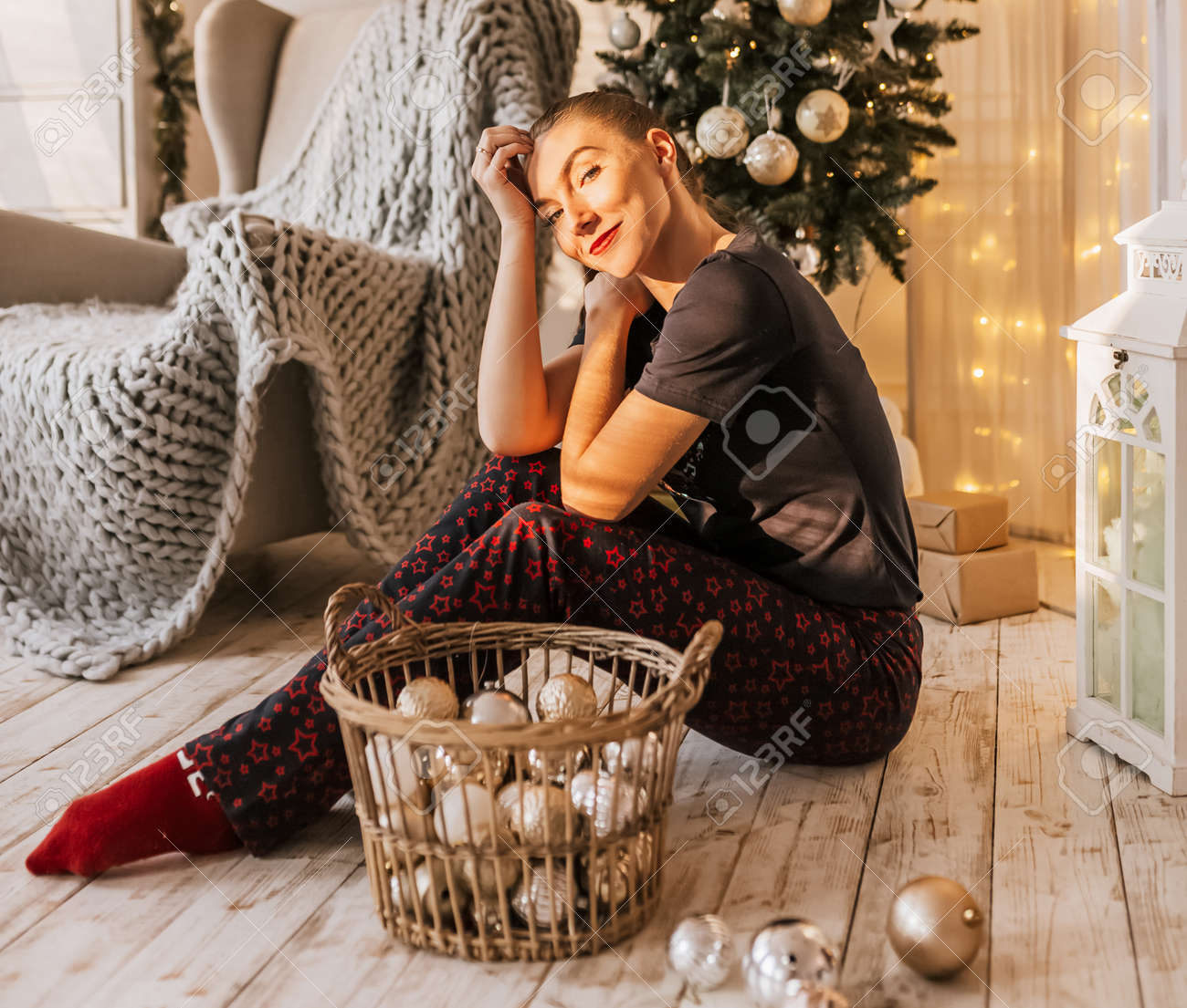 Beautiful cheerful happy young girl on the floor in pajamas with christmas toys near the new year tree at home - 173923688