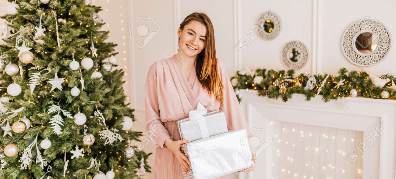Wish you a Merry Christmas. Girl with a gift presents. Happy feeling to New Year. - 173923435