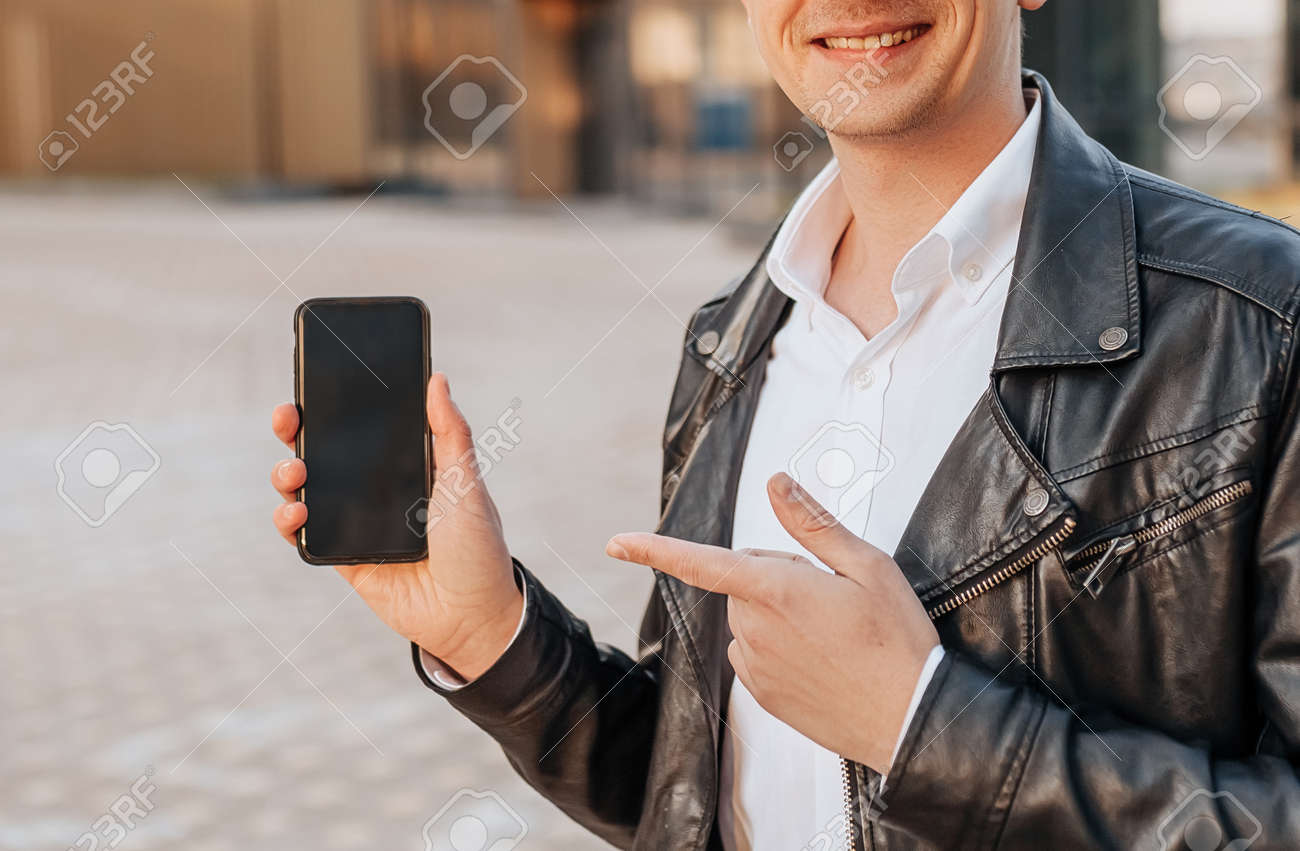Handsome with a smartphone on the street of a big city. Businessman points finger at phone screen on urban background - 173945770