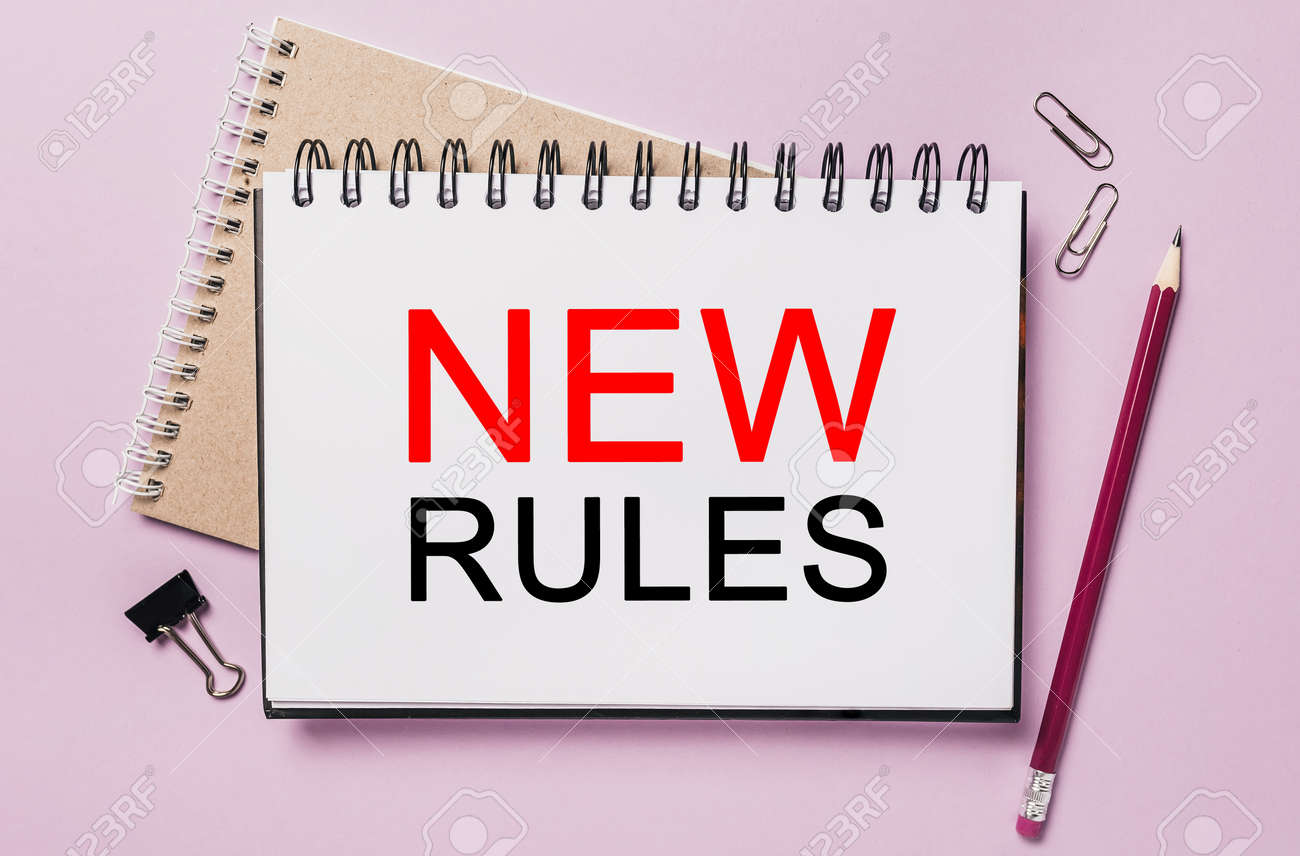 Text new rules on a white sticker with office stationery background. Flat lay on business, finance and development concept - 173945777