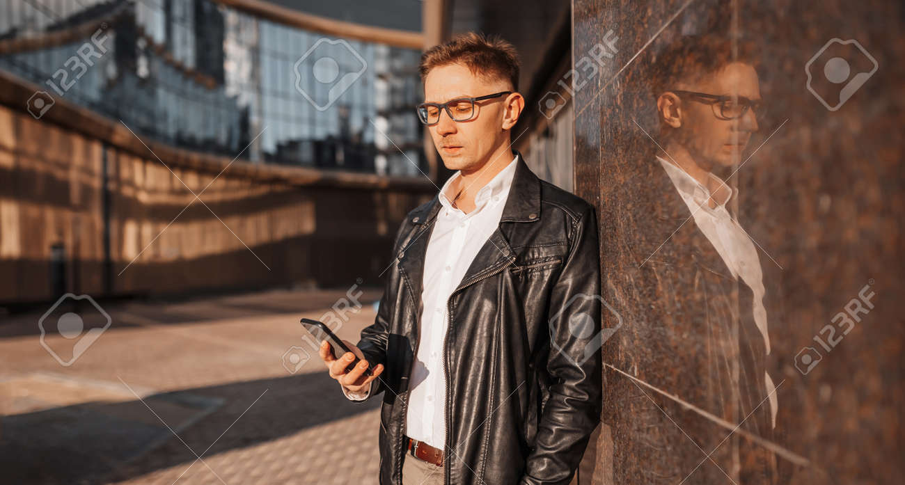 Handsome man with glasses with a smartphone on the street of a big city. Businessman talking on the phone on urban background - 173945875