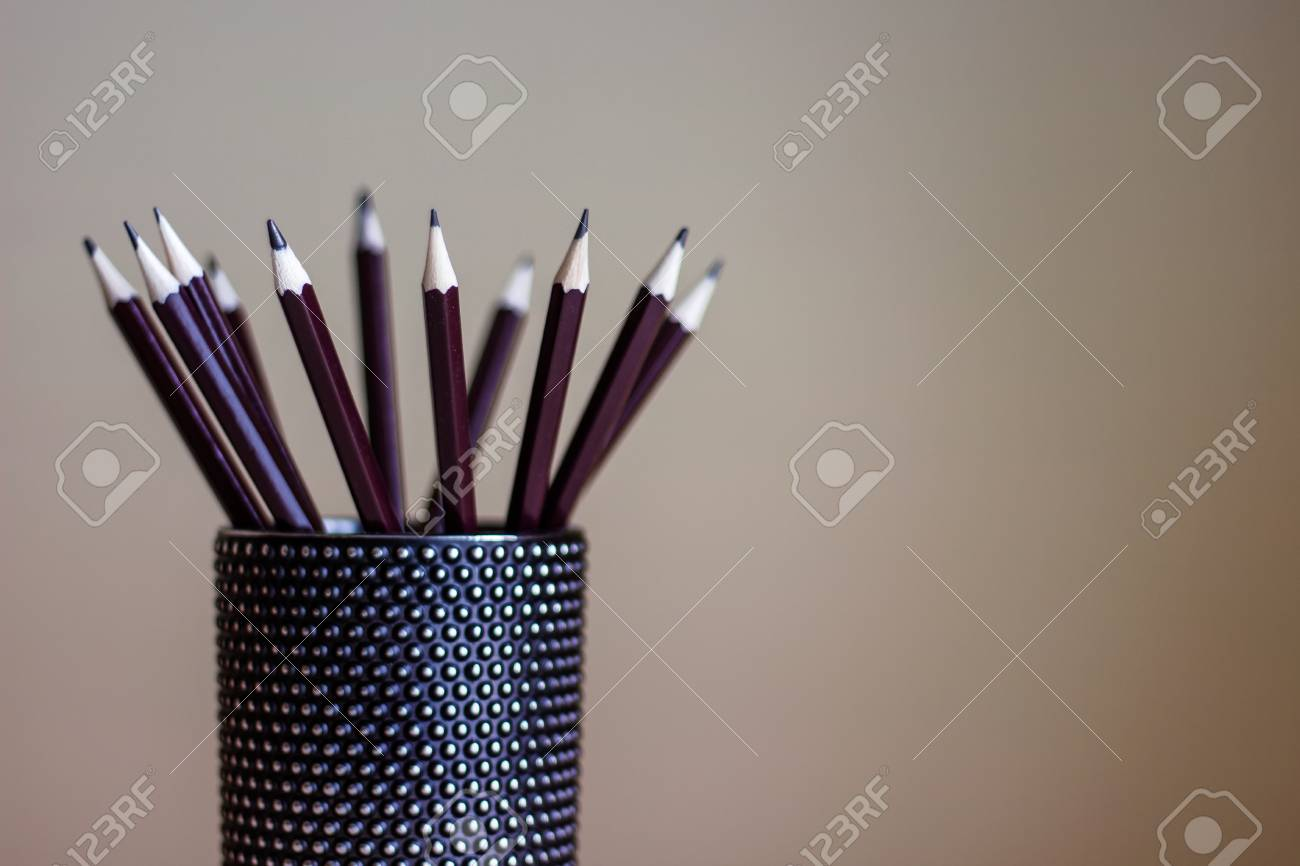 many graphite pencils standing in black glass container drawing