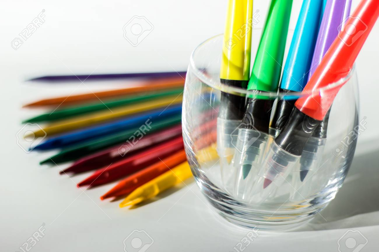 drawing utensils colorful crayon pencil and markers in a glass