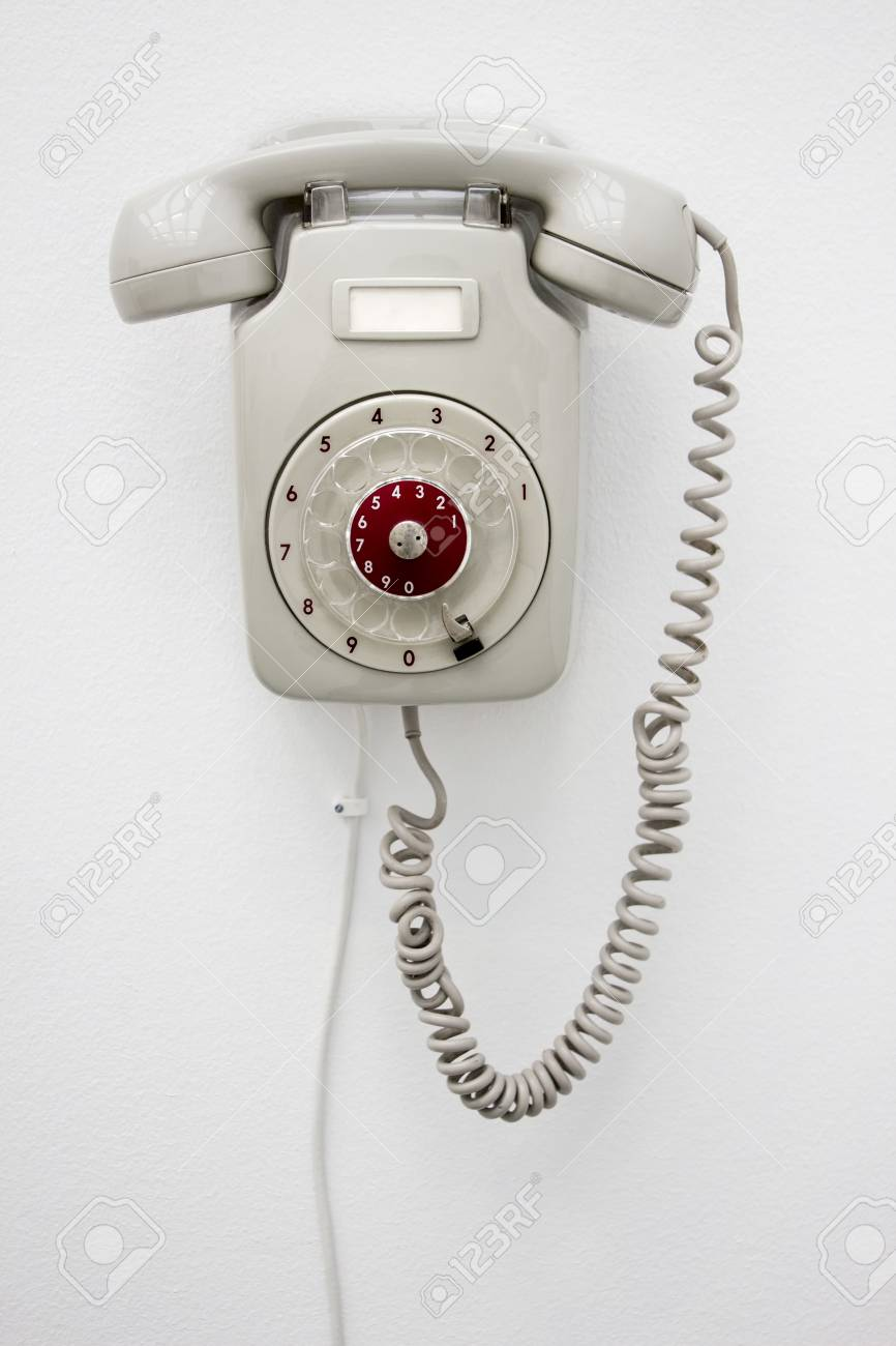 Old fashioned gray rotary telephone hanging on white wall  Vertical