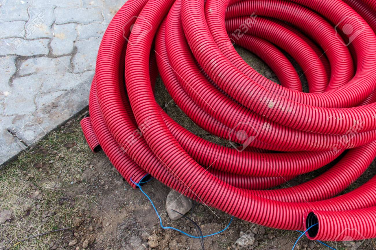 Red plastic pipes for underground electrical wires lying on the.. on