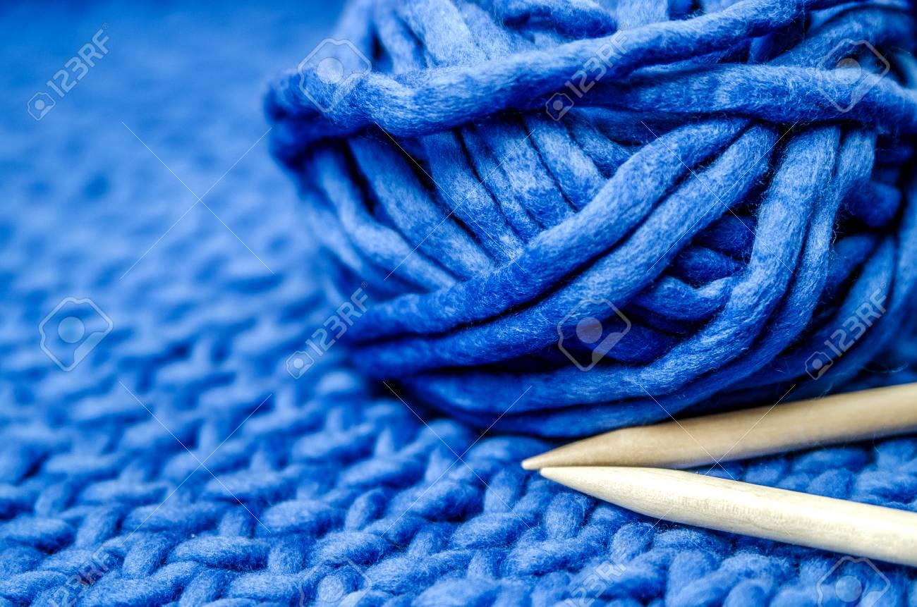 Plaid Fatto Ai Ferri un fascio di filato blu merino e ferri da maglia in bambù su un plaid blu  legato.