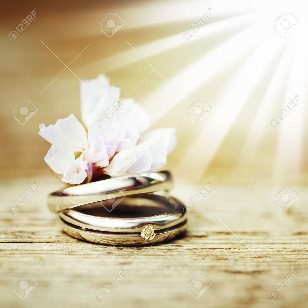 Wedding Engagement Rings Close Up With Cute Wild Flower On Wood