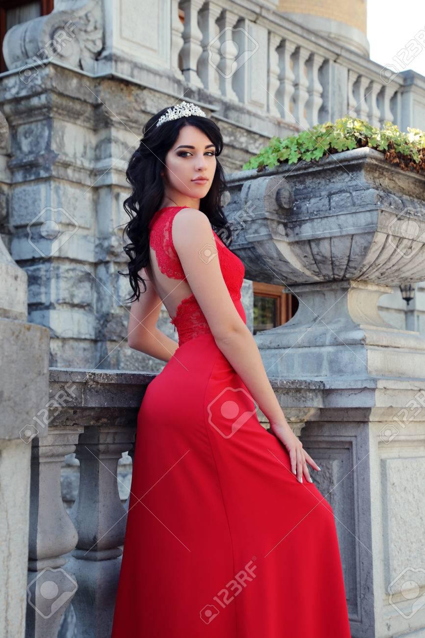 d8441ee3895e De fotografía de moda al aire libre de la mujer magnífica con el pelo  oscuro lleva vestido rojo de lujo y accesorios, que presenta en chalet antic
