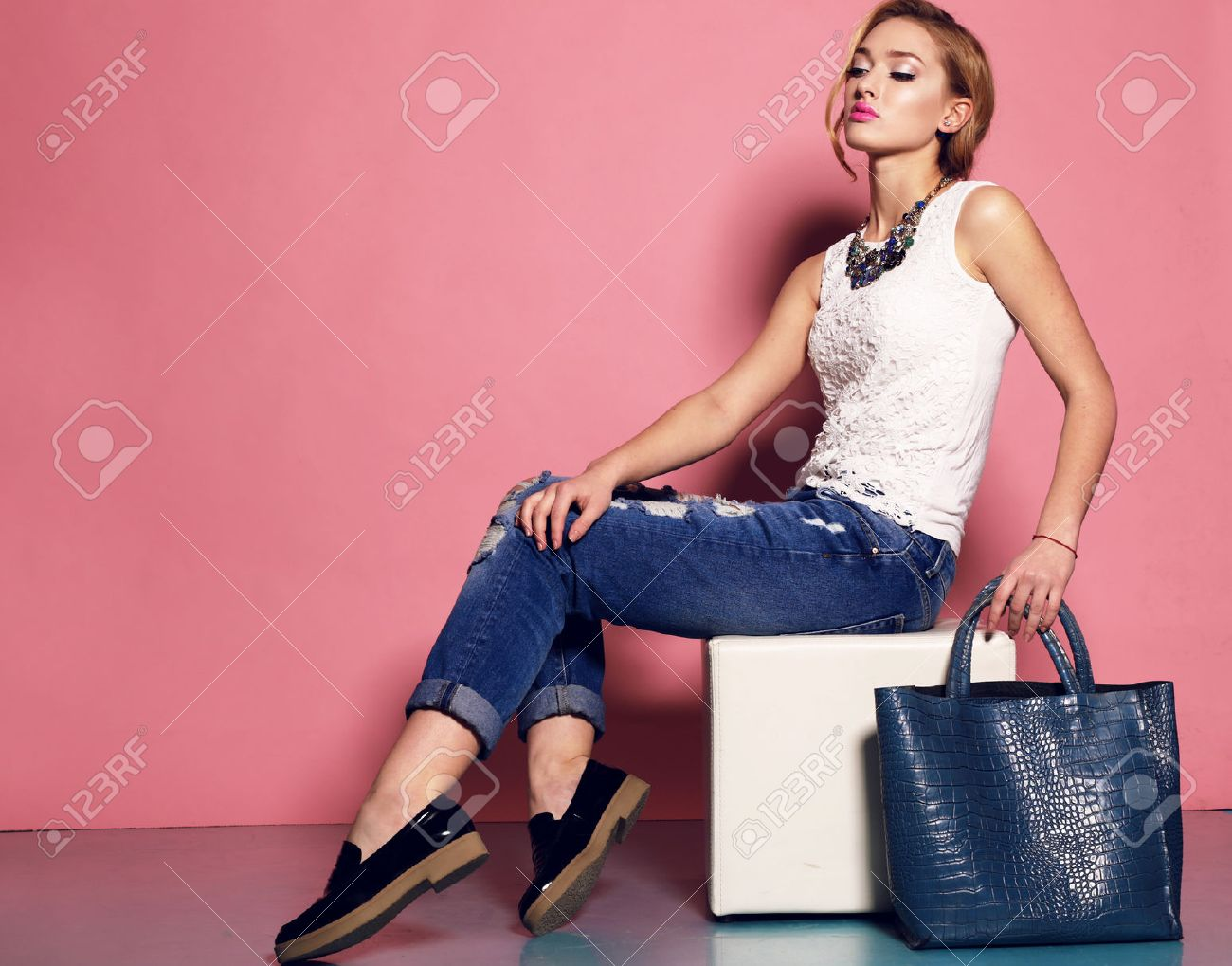 fashion studio photo of gorgeous young woman with blond curly hair wears elegant blouse and jeans,holding a big bag in hands Stock Photo - 47708608