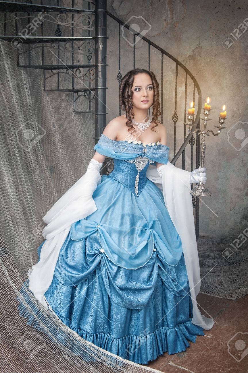 Beautiful Young Woman In Long Blue Medieval Dress With Candelabrum ...