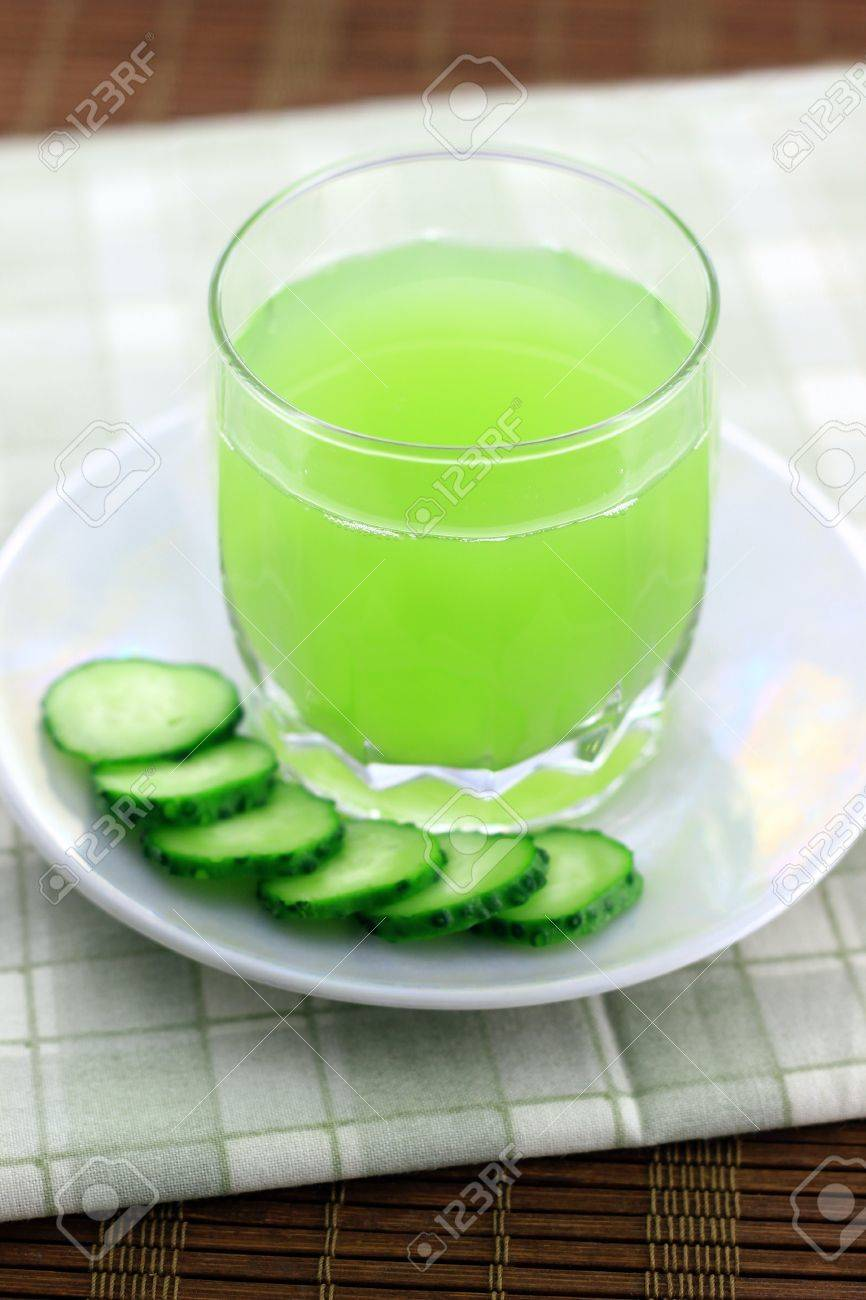 Cucumber juice next to cucumber slices - 21263574